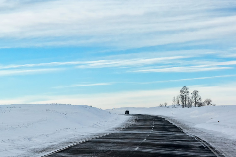 winter road in the Russian steppe, snow drifting