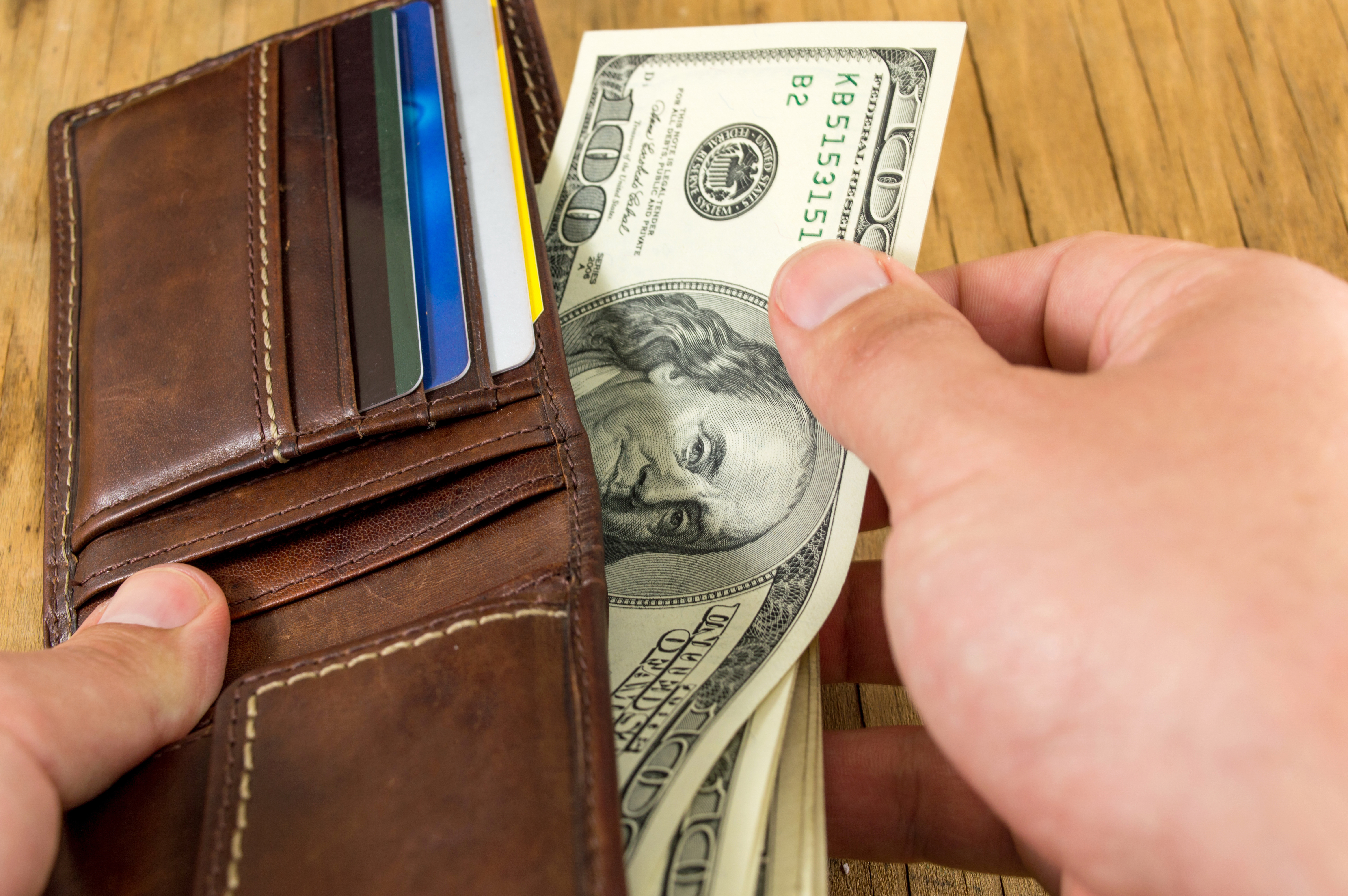 Male hand taking dollar out of a leather wallet